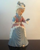 Vintage Christmas Caroler Woman Carol 14 inches     Beautiful Bisque Christmas Caroler   From the Sugarplum Collection.     This figure is a woman holding a song book. She stands 14 inches tall and 8 inches wide. She wears a blue victorian gown with a pink and white jacket, white hat, and blue gloves.