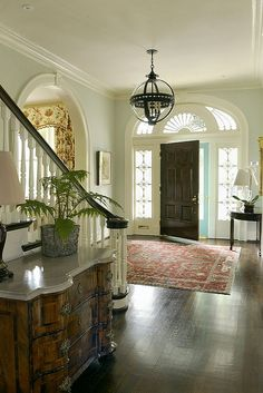 By Matthew Carter Interiors.  Dark door and staircase bannister.  Lovely antique chest and carpet.