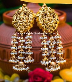 This exquisite arrangement of Nakshi work Lakshmi amidst twin peacock studs and intricate long mini pearl jhumkas will never go . Gold Jhumka Earrings, Jewelry Design Earrings, Gold Earrings Designs, Antique Earrings, Pearl Jhumkas, Gold Designs, Big Earrings, Bridal Earrings, Jewelry Necklaces