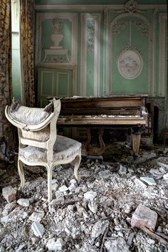 Crumbled ceiling, piano and a broken char in what was one probably once a beautiful room.