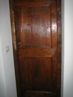 La vecchia porta in abete della foto precedente, allungata, restaurata e collocata in un'interno come porta di un bagno.