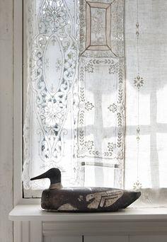 vintage white linens as curtains and primitive decoy