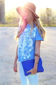 Floppy hat, floral printed tee, colorful stacked wrist, white skinnies and cobalt clutch
