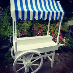 A traditional looking white cart often used at wedding for candy floss or a candy bar. This is plain white allowing you to customise it. We have 5 different changeable canopies for it, red and white large Gingham, pink and white small Gingham, black and white striped, blue and white striped, and champagne. Add you own accessories to really make it yours. Hire for £100