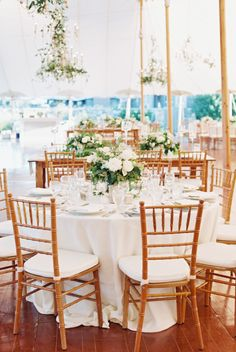 light bright reception tent with wood chairs and dripping florals | Photography: Carmen Santorelli