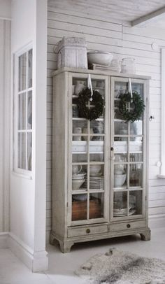 Armoire hutch with glass doors, and those perfect boxwood wreaths love love love
