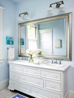 Clean and Serene  To keep renovation costs down, the homeowners kept the Chippendale-style vanity but revived it with crisp white paint. To avoid water damage, the wood countertop received several coats of high-gloss enamel paint. To lighten up the room, the homeowners chose soft blue paint for the walls and ceiling, and the existing trimwork was painted white. A mirror with a silver frame and new sconces bring out a refreshed vintage style. A pocket door  conceals the new toilet