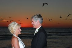 Married couple at sunset with lots of birds flying in the background.