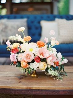 Unique floral arrangement with orange and blush poppies, ranunculus, and garden roses in a gold container.