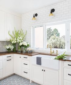 White kitchen with patterned tile floor and butcher block counters