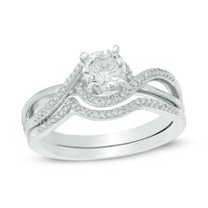 Your love shines brightly with this dazzling bridal set. Crafted in sterling silver, the engagement ring features a 5.5mm lab-created white sapphire center stone wrapped in a swirling bypass of diamond accents that create the ring's split shank. The coordinating diamond-lined contoured wedding band completes this shimmering ensemble. Captivating with a total of 1/10 cts. of diamonds and buffedto a brilliant luster, this wedding set is sure to win her heart. Custom made to fit her rin...