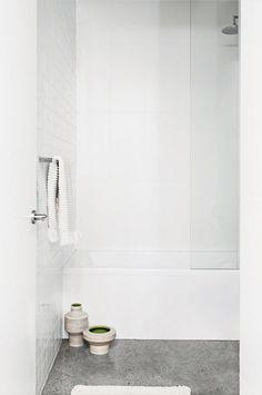 All-white bathroom, grey polished concrete floor, shower over bathtub