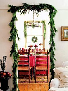 Drape doorways in evergreen for a festive look. More festive holiday decor: www.bhg.com/christmas/indoor-decorating/gala-holiday-dining-rooms/?socsrc=bhgpin102312deckthedoors#page=3