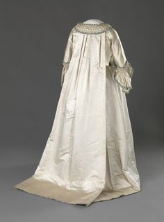 Rear view of Wedding Dress, 1760, Norway, Hand Woven silk satin. Hand Woven, glazed linen and machine woven cotton fabric (secondary) plain weave. Silk Trimmings, whalebone boning. Hand Stitching. Digitalt Museum - Brudekjole