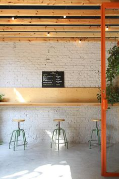 Combination of white exposed brick wall, concrete floor, timber ceiling, bar height seating, and little flicker of lights. Café Bistro, Timber Ceiling, Exposed Brick Walls, Bath And Beyond Coupon, Herd, Concrete Floors, Concrete Ceiling, Restaurant Design, Oak Restaurant