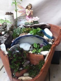 a fairy garden using a clay pot and broken pottery, dishes, etc.