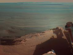 Its hard not to personify NASAs Mars rovers. Here, the rover Opportunity seems to peer out bravely into the great unknown Martian landscape.   Opportunity used its panoramic camera to capture this view of Endeavour Crater on March 9, 2012 during the late afternoon (Mars time, of course). The rover has been exploring the western rim of Endeavour Crater since August 2011. The crater spans 14 miles (22 km) in diameter, about the size of Seattle.