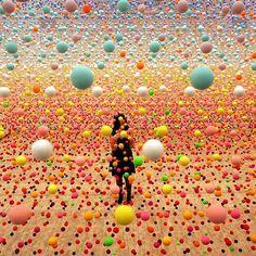 "Sydney artist Nike Savvas stands inside her infinite-seeming installation of bouncy balls suspended on clear nylon thread ""Atomic: Full of Love, Full of Wonder."""