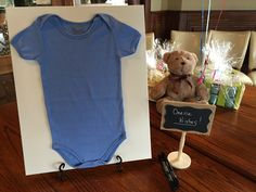 Guests sign or write a wish on a baby onesie