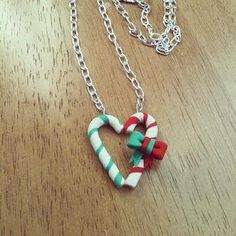 Candy Cane pendant polymer clay by FlowerChildCharms on Etsy  this pendant is two candy-canes, a red one and a green one shaped to make a heart with a bow of red and green on one of the candy-canes.