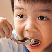 Young boy eating healthy breakfast credit iStockphoto.com/Sirichai Chitvises