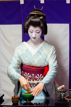 Jikata Geiko Masaki preparing tea. Masaki is a very Special Lady because she debuted directly as a geiko in Gion Higashi and devoted herself to playing Instruments. As a Jikata she normally would not be as famous but her allure and impecable style have made her very popular. Here she Sports a delicate water wave Hiki in White. It seems like she's wearing a Kimono made of seafoam!