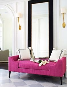 A large mirror and bright couch create a vibrant and memorable entryway.