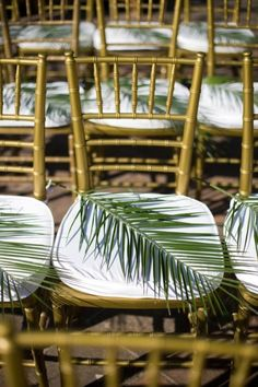 chairs with palm fronds / photographed by Corbin Gurkin- chivari chairs, white pads and a palm leaf... Very Tiki Px