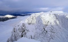 A walker traverses the snow-covered Cairn Lochan summit on the Cairngorm Plateau, near Aviemore, Scotland