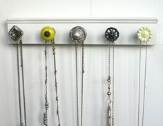 Put cute knobs on a piece of wood to make a necklace holder
