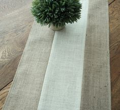 Thank you to a wonderful customer for asking me to create this gorgeous table runner! I just had to list it! The burlap table runner is hand made from both natural and ivory burlap. It has such an updated rustic modern look to it and blends beautifully with all styles of decor. The table runner measures 14 wide. Contact me for any custom size. I have many styles of runners in my shop. You can see them here: http://www.etsy.com/shop/theruffleddaisy?section_id=102007...