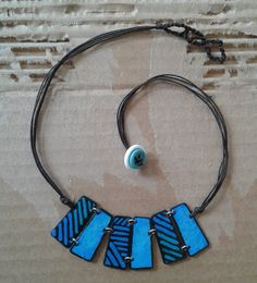 Blue colors and geometrical shapes compose a special handpainted necklace.  A little piece of art just on your neck!  Stainless steel is cut by