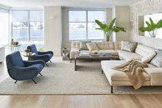 Sectional sofa, bamboo wallpaper and lady chairs complete this room in Tribeca