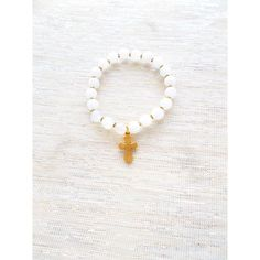 """This collection is called """"Rainy Days"""" and embodies the whirlwind of emotions that the sky and earth go through as the storm begins , peaks, and concludes. White jade 4mm rounds accompanied by gold fill spacers and finished with a gold fill cross charm."""
