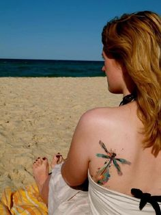An exploding dragonfly tattoo on the back. The dragonfly looks as if it is exploding with colors and that's what makes the design stand out even form afar.