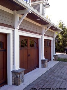 An arched garage door window design accentuates these handsome and rich wood tone garage doors.  White trim framing the door adds additional style and detail.