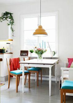 Une salle à manger immaculée et ses meubles colorés