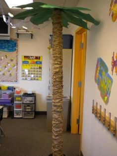 DIY palm tree for a beach themed classroom made from an empty carpet roll, brown paper bags, a bucket, an umbrella and poster board