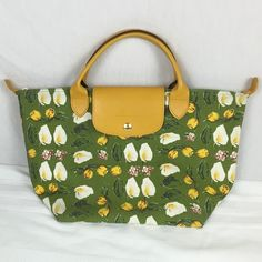 """Longchamp Purse Bag Green/Yellow Floral Pattern This is a great spring-themed handbag with bright green and yellow colors. Zippered close. Leather handle and close flap that snaps in place.  Bag measurements width measured at base: HxLxW 10""""x15.5""""x7"""" (width measured at bottom) If you have questions or comments, please let me know. Thank you for viewing this listing. Be well and have a blessed day. Longchamp Bags Totes"""