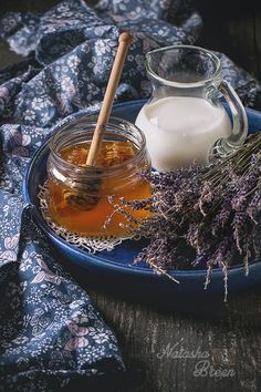 Honey, Milk and Lavender - Open glass jar of liquid honey with honeycomb and honey dipper inside, glass jug of milk and bunch of dry lavender in big blue ceramic plate over old wooden surface with blue textile rag. Dark rustic style.