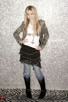 Hannah Montana outfit: Grey denim jacket, white top, jeans, black Jeweled skirt, boots