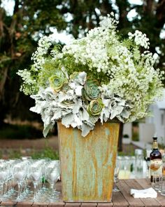 A large arrangement of Queen Anne's lace, dusty miller, and succulents in muted fall shades anchored the bar