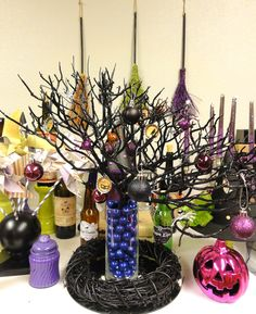 - Vase: 99cents from the dollar store   - Vase Filling: grape flavored gum balls  - Wicker Wreath: donated to Hospice of Yuma & painted black with spray paint  - Branches: purchased from from save-on-crafts.com & spray painted black  - Purple Jar: purchased from the dollar store, panted purple on the inside  - Bottle Cap Halloween Ornaments: hand made by Carol Davis.   - Glittered Witch Brooms: Purchased from Target