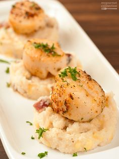 Seared Scallops with Creamy Bacon Grits - to complement their sweet, succulent flavor, these pan-seared scallops are served atop a bed of creamy grits with bacon, sautéed onion and fresh corn.