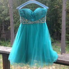 Turquoise strapless prom dress Turquoise blue, sweetheart neckline strapless dress. Tulle overlay skirt with ruffled bottom. Blue silk Corset back. Sequin waist. Hannah S Dresses Prom