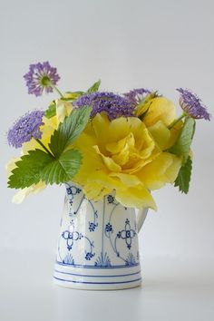 blue and yellow flowers in blue and white pitcher - lovely