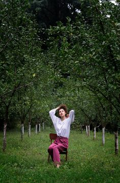 Fashionable woman sitting in a chair in a tree orchard