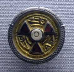 Silver disc brooch with gilding. Central setting of shell and three red garnet triangle insets.