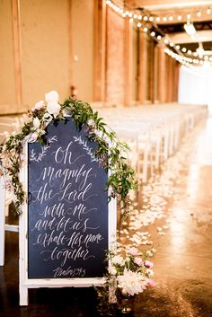 Ceremony sign with Psalms 34:3 with floral. Photo by Andrea Elizabeth Photography. Venue at McKinney Cotton Mill.