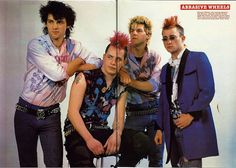 "A colorful Lot, these. This is punk band Abrasive Wheels, and there's something quite colorful and fun about the eighties style transmutation than what passes for 'style' today. Vocalist Phil ""Shonna"" Rzonca is seen at far right, sporting early punk's popular (but now largely passe) hijacking of the 50's dress coat clashed with punk's more autonomous elements: studded Belts, tight pants, and rips. No band today would dare venture into this territory, but it is sorely missed."